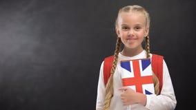 Het glimlachen van het vrouwelijke handboek van de leerlingsholding met de gedrukte vlag van Groot-Brittannië, talen stock videobeelden