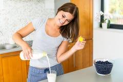 Het glimlachen van vrouwen gietende melk in glas Stock Afbeelding