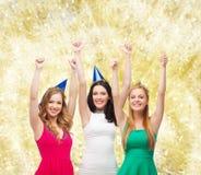 Het glimlachen van vrouwen in partijkappen het tonen beduimelt omhoog stock afbeelding