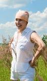 Het glimlachen van vrouwentribunes op weide bij zonnige dag Stock Fotografie