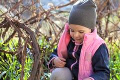 het glimlachen van warm gekleed meisje in een GLB zit op haar knieën onder de bloemen van blauwe sneeuwklokjes in de wijngaard royalty-vrije stock foto's