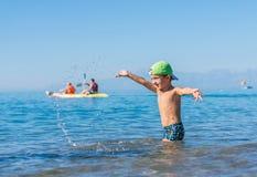 Het glimlachen van weinig babyjongen in groen honkbal GLB die en in het overzees, oceaan spelen bespatten Positieve menselijke em stock fotografie