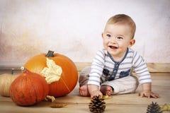 Het glimlachen van weinig babyzitting op de vloer met pompoenen Royalty-vrije Stock Afbeeldingen