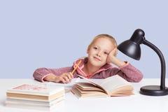 Het glimlachen van weinig charmant meisje zit bij lijst, doet thuiswerktaak samen met haar moeder, probeert om samenstelling te s stock afbeeldingen