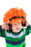 Het glimlachen van weinig jongen die aan muziek in headphon luistert Stock Foto