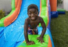 Het glimlachen van weinig jongen die onderaan een opblaasbaar spronghuis glijden Stock Foto's