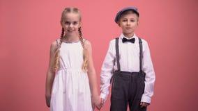 Het glimlachen van weinig jongen en meisje die de handen van de cameraholding op roze achtergrond onderzoeken stock videobeelden