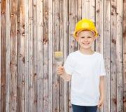 Het glimlachen van weinig jongen in helm met verfborstel Stock Foto's