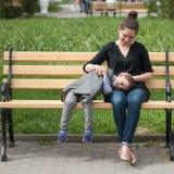 Het glimlachen van weinig jongen ligt op zijn moeder` s heupen zittend op de bank Stock Afbeeldingen