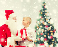 Het glimlachen van weinig jongen met de Kerstman en giften Stock Foto