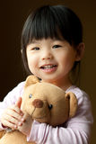 Het glimlachen van weinig kind met een teddybeer Stock Foto