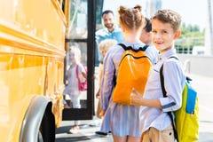 het glimlachen van weinig schooljongen die schoolbus met klasgenoten ingaan terwijl leraar status royalty-vrije stock afbeelding