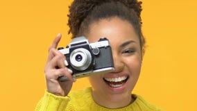 Het glimlachen van zwarte vrouwelijke nemende foto door ouderwetse camera, creatieve hobby, vrije tijd stock videobeelden