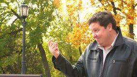 Het glimlachen het vette mens komt tonen dichter gebaar met vinger in de herfstpark stock footage