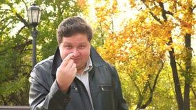 Het glimlachen het vette mens komt tonen dichter gebaar met vinger in de herfstpark stock videobeelden