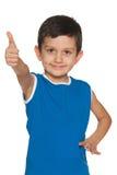 Weinig jongen in blauw houdt zijn duim tegen Royalty-vrije Stock Fotografie