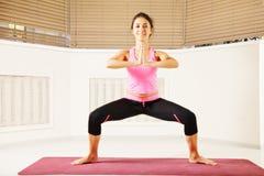 Het glimlachen vrouw de status in yoga stelt Stock Afbeelding
