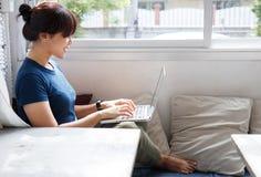 Het glimlachen vrouw het letten op video op laptop computer in comfortabele coworking binnenlandse, vrouwelijke studentenrust tij royalty-vrije stock afbeelding