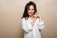 Het glimlachen vrouwelijk model in wit overhemd, op een beige achtergrond, die gekruiste vingers houden stock afbeelding