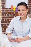 Het glimlachen vrouwelijk uitvoerend tekstoverseinen in bureau stock foto's