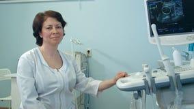 Het glimlachen vrouwelijke artsenzitting naast ultrasone klank kenmerkend apparaat Stock Afbeelding