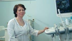 Het glimlachen vrouwelijke artsenzitting naast ultrasone klank kenmerkend apparaat stock footage