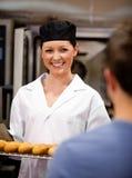 Het glimlachen vrouwelijke baguettes van de bakkersholding met cliënt royalty-vrije stock foto