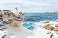Het glimlachen vrouwelijke, gelukkige dagen die in de de zomerzonneschijn door de oceaan zonnebaden stock foto's