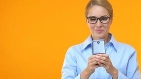 Het glimlachen het vrouwelijke manager typen op smartphone, die in sociale media op het werk babbelen stock footage