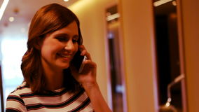 Het glimlachen het vrouwelijke uitvoerende spreken op mobiele telefoon in gang stock footage