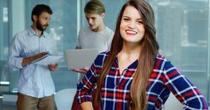 Het glimlachen vrouwelijke uitvoerende status met handen op heup terwijl collega's die op achtergrond bespreken stock video