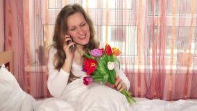 Het glimlachen vrouwelijke vrouwenzitting op bed met boeket van bloemen en het roepen van minnaar stock videobeelden