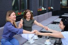 Het glimlachen vrouwen het houden overhandigt dichtbij koppen van koffie bij koffie Stock Foto