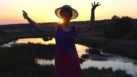 Het glimlachen vrouwendansen op een meerbank bij zonsondergang stock footage
