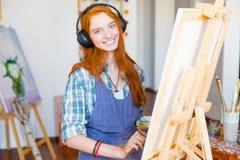 Het glimlachen vrouwenkunstenaar het schilderen op canvas en het luisteren aan muziek royalty-vrije stock foto
