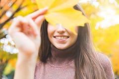 Het glimlachen vrouwenportret met een geel blad in de herfst Royalty-vrije Stock Foto