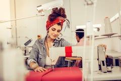 Het glimlachen vrouwenzitting bij de lijst met naaimachine stock afbeelding