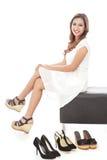 het glimlachen vrouwenzitting naast paren schoenen Royalty-vrije Stock Foto's