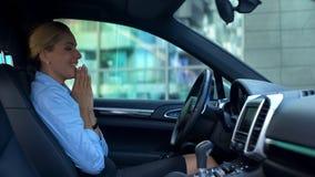 Het glimlachen vrouwenzitting in nieuwe auto, tevreden met de luxedienst tijdens aankoop royalty-vrije stock afbeeldingen