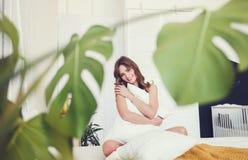 Het glimlachen vrouwenzitting op bed stock foto