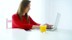 Het glimlachen vrouwenzitting op wit huiskantoor en het werken aan laptop stock videobeelden