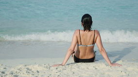 Het glimlachen vrouwenzitting op zandig overzees strand stock video