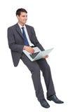 Het glimlachen zakenmanzitting die laptop met behulp van Royalty-vrije Stock Afbeeldingen