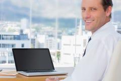 Het glimlachen zakenmanzitting voor laptop Royalty-vrije Stock Foto