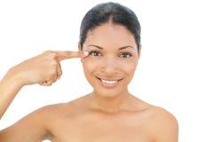 Het glimlachen zwart haired model die op haar oog richten Stock Fotografie