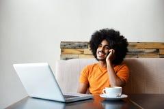 Het glimlachen zwarte kerelzitting bij koffie met laptop en cellphone Royalty-vrije Stock Fotografie