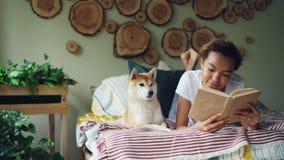 Het glimlachende Afrikaanse Amerikaanse studenten mooie meisje leest thuis boek op bed terwijl haar huisdierenhond dichtbij haar  stock videobeelden