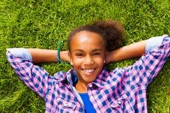 Het glimlachende Afrikaanse meisje met in de zomer legt op gras Royalty-vrije Stock Afbeeldingen