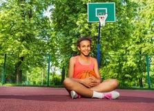 Het glimlachende Afrikaanse meisje zit op speelplaats met bal Royalty-vrije Stock Foto