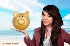 Het glimlachende Aziatische spaarvarken van de bedrijfsvrouwenholding stock foto's